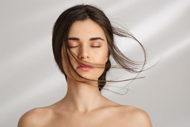 Mulher bonita após procedimentos de spa, se divertindo. olhos fechados.