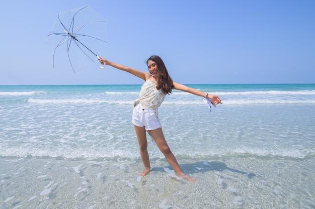 Mulher bonita, aproveitando a praia com um guarda-chuva