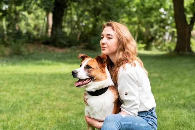 Mulher bonita, aproveitando o tempo lá fora com cachorro