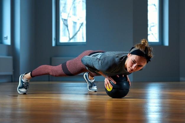 Mulher bonita apta no sportswear posando enquanto está sentado no chão com basquete na frente da janela no ginásio esporte e estilo de vida saudável menina
