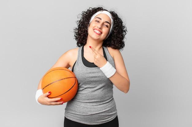 Mulher bonita árabe parecendo animada e surpresa, apontando para o lado e segurando uma bola de basquete. conceito de esporte