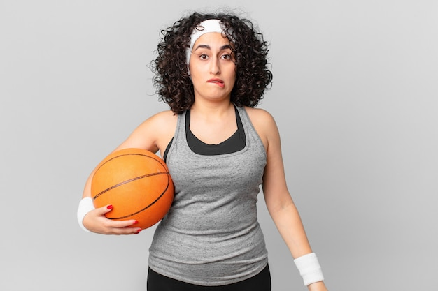 Mulher bonita árabe parecendo perplexa e confusa e segurando uma bola de basquete. conceito de esporte