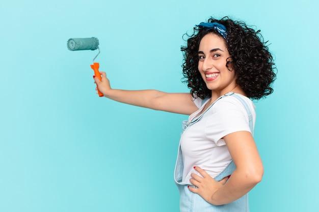 Mulher bonita árabe pintando o conceito de parede de casa
