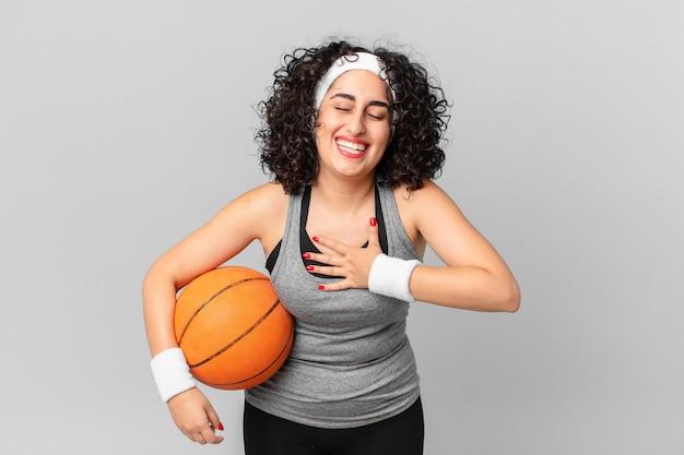 Mulher bonita árabe rindo alto de uma piada hilária e segurando uma bola de basquete. conceito de esporte