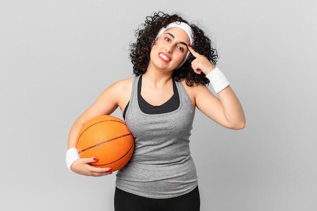 Mulher bonita árabe se sentindo confusa e intrigada, mostrando que você é louco e segurando uma bola de basquete. conceito de esporte