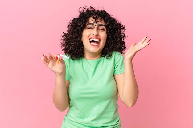 Mulher bonita árabe se sentindo feliz e surpresa com algo inacreditável. conceito de não fumar
