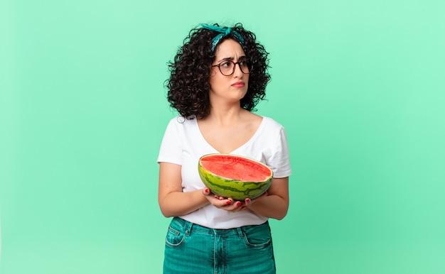 Mulher bonita árabe se sentindo triste, chateada ou com raiva e olhando para o lado e segurando uma melancia. conceito de verão