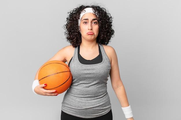 Mulher bonita árabe se sentindo triste e chorona com um olhar infeliz e chorando e segurando uma bola de basquete. conceito de esporte Foto Premium