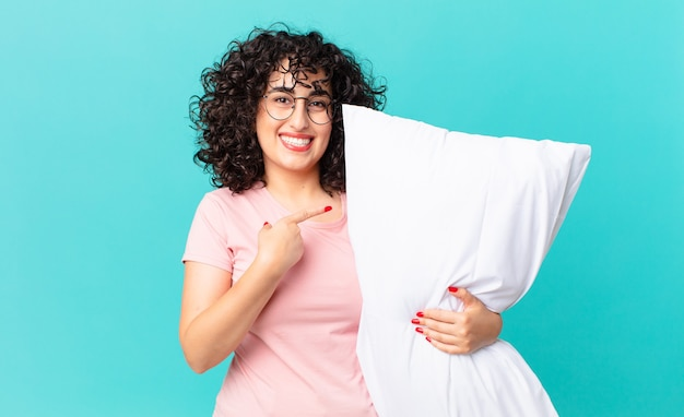 Mulher bonita árabe sorrindo alegremente, sentindo-se feliz e apontando para o lado. vestindo pijama e segurando um travesseiro
