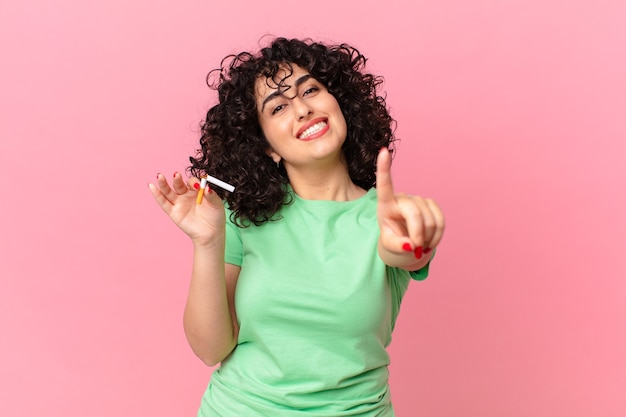 Mulher bonita árabe sorrindo com orgulho e fazendo o número um com confiança. conceito de não fumar