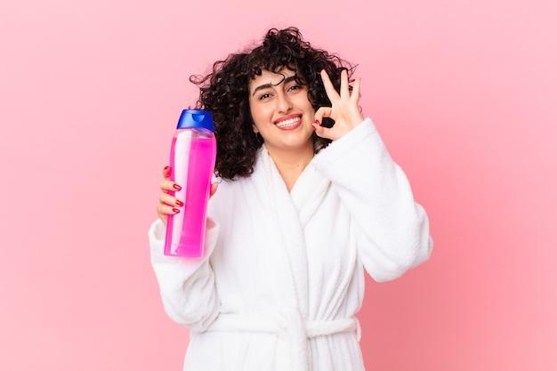 Mulher bonita árabe vestindo roupão de banho e segurando um frasco de xampu
