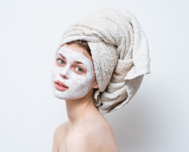 Mulher bonita arrumando máscara facial branca e toalha na cabeça