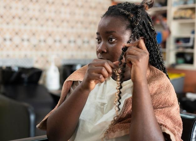 Mulher bonita arrumando o cabelo no salão de beleza