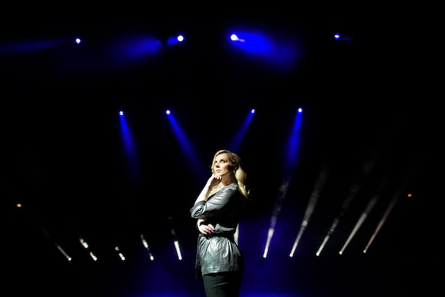 Mulher bonita artista sobre o fundo de holofotes borrados no palco