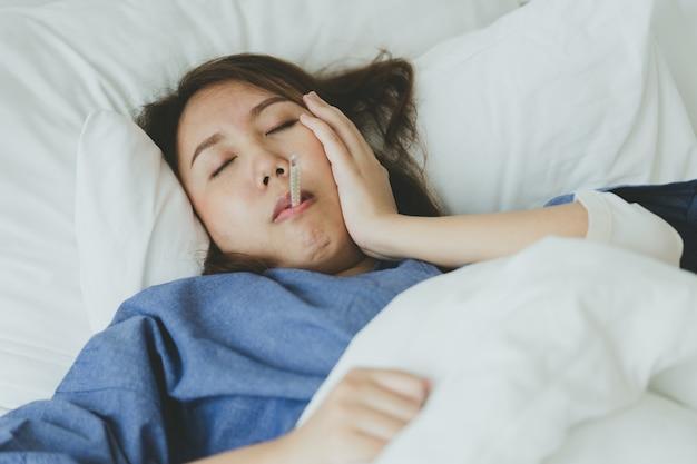 Mulher bonita asiática a hipotermia foi medida pela febre. deitar na cama