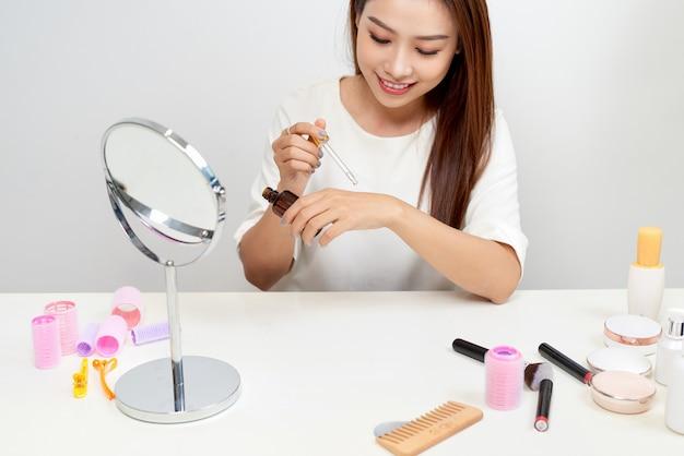 Mulher bonita asiática colocando soro cosmético na mão dela enquanto está sentado na penteadeira.