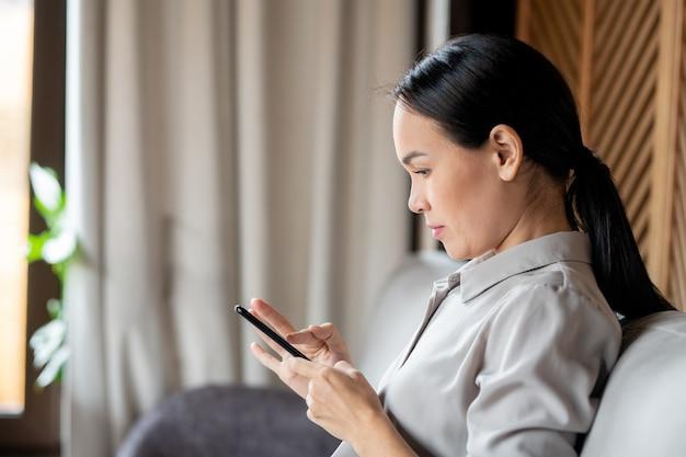 Mulher bonita asiática com cabelo comprido escuro rolando ou enviando mensagens de texto no smartphone enquanto está sentada no sofá