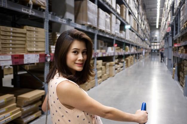 Mulher bonita asiática com cara sorridente, empurrando um carrinho está à procura de alguns itens no armazém