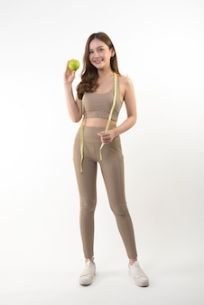 Mulher bonita asiática com maçã e fita métrica