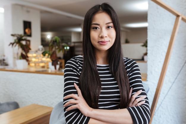 Mulher bonita asiática com os braços cruzados na cafeteria