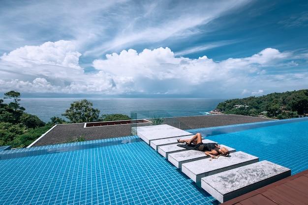 Mulher bonita asiática com os olhos fechados relaxa perto da piscina de beiral infinito. modelo descansando em uma vivenda de luxo