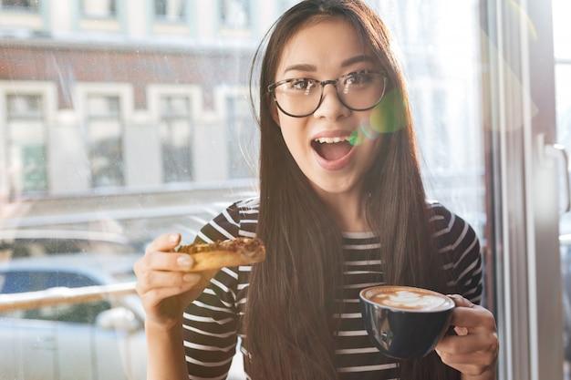 Mulher bonita asiática comendo bolo no peitoril da janela