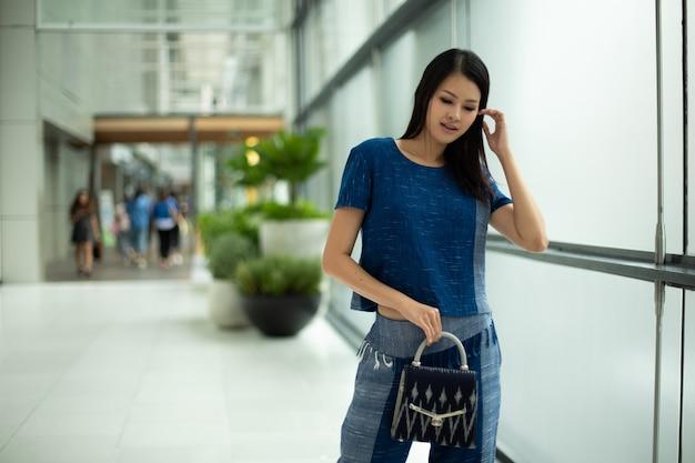 Mulher bonita asiática em azul índigo vestido de algodão local apresenta nova coleção de roupas prontas para vestir em loja de moda que tem grandes janelas e fundo desfocado para logotipo de texto de espaço de cópia