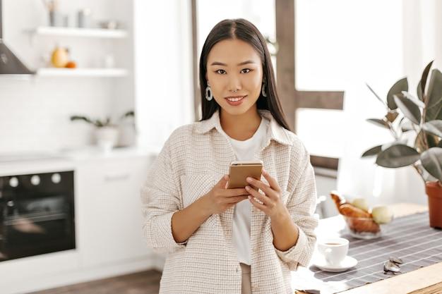 Mulher bonita asiática em um cardigã bege e camiseta branca posa com o telefone na cozinha