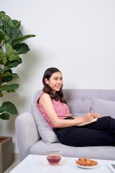 Mulher bonita asiática escrevendo no sofá em casa na sala de estar
