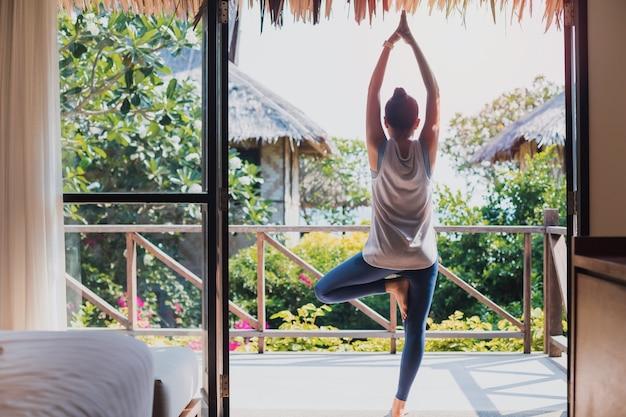 Mulher bonita asiática exercita e joga ioga em casa. conceito de exercício durante a quarentena em casa para prevenir o coronavírus e a infecção por covid-19.