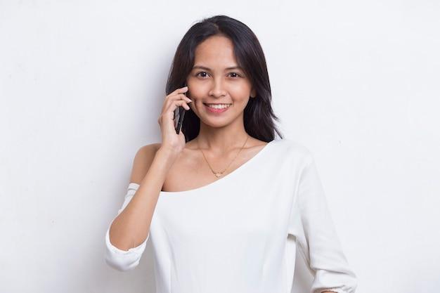 Mulher bonita asiática jovem feliz usando telefone celular isolado no fundo branco