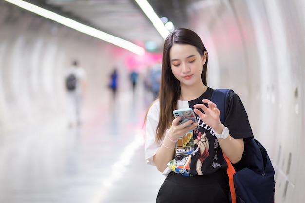 Mulher bonita asiática jovem parada no estilo de vida do túnel do metrô enquanto segura o smartphone na mão