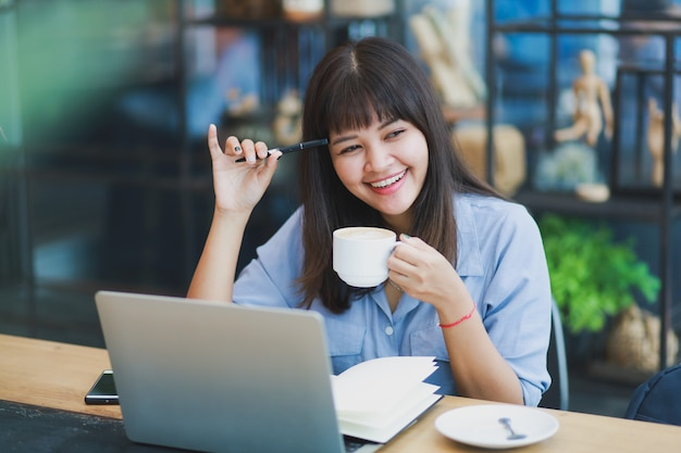 Mulher bonita asiática na camisa azul usando laptop e bebendo café