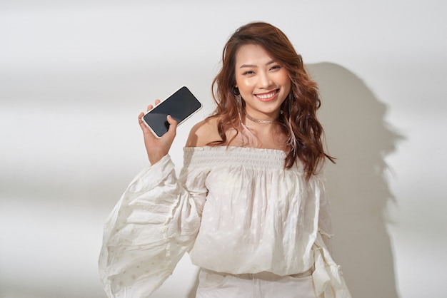 Mulher bonita asiática no casual wear segurando o smartphone em uma mão, dançando