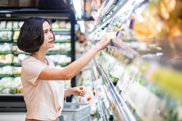 Mulher bonita asiática nova que guarda a cesta do mantimento que anda no supermercado.