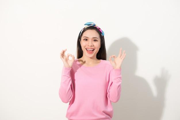 Mulher bonita asiática nova que mostra o sinal de ok com as duas mãos. feche o retrato.