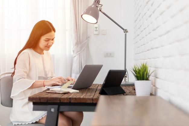 Mulher bonita asiática nova que usa o portátil em casa.