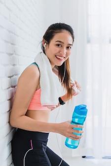 Mulher bonita asiática que descansa e que guarda a garrafa de água após a ioga do jogo e o exercício no fundo branco da parede de tijolo.