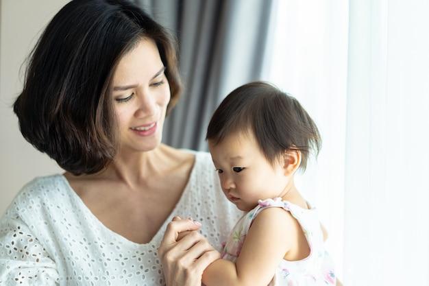 Mulher bonita asiática que guarda a mão inocente do bebê na sala em casa.
