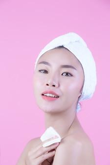 Mulher bonita asiática que limpa a cara em um fundo, em uma cosmetologia e em uns termas cor-de-rosa.