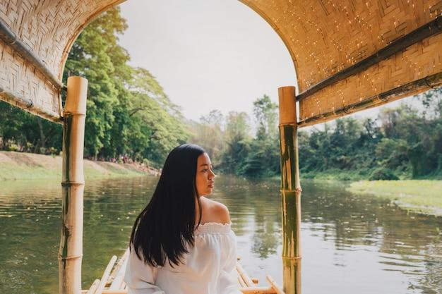 Mulher bonita asiática que viaja em um cruzeiro de madeira da jangada abaixo dos rios de tailândia rural com fundo verde da floresta.