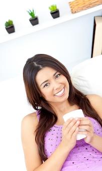 Mulher bonita asiática segurando uma xícara de café em casa