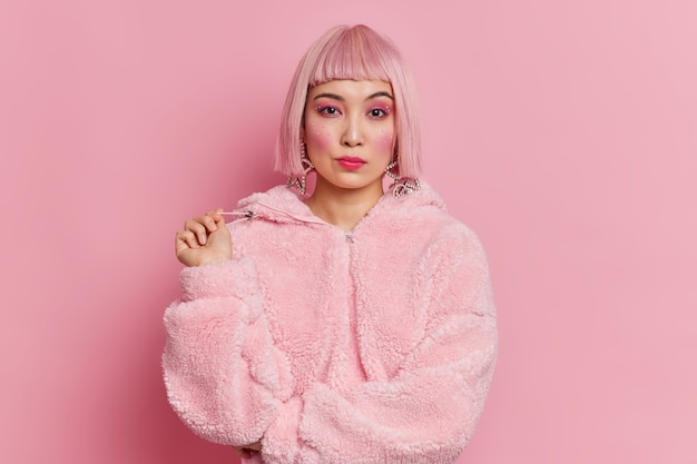 Mulher bonita asiática séria com cabelo rosa da moda, vestida com um casaco de inverno, fazendo poses de maquiagem vivas