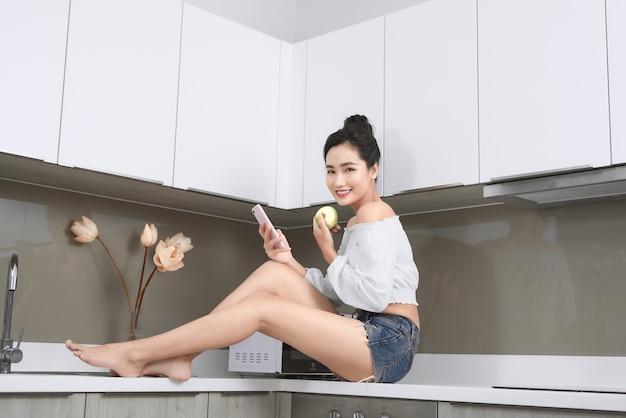 Mulher bonita asiática sorridente, olhando para o celular e segurando uma maçã na cozinha.