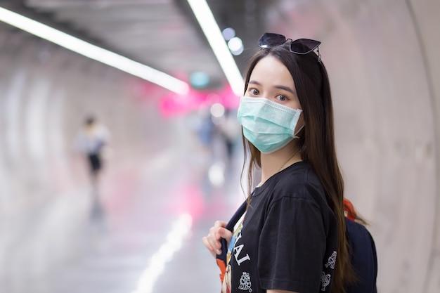 Mulher bonita asiática usa camisa preta e máscara médica enquanto caminha pelo túnel do metrô