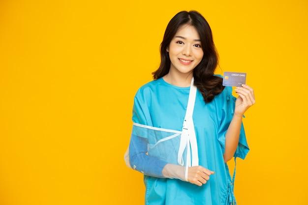 Mulher bonita asiática vestindo paciente segurando o cartão de crédito isolado na parede amarela.