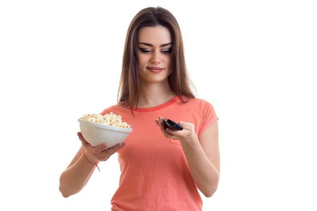 Mulher bonita assistindo tv com pipoca isolada no fundo branco