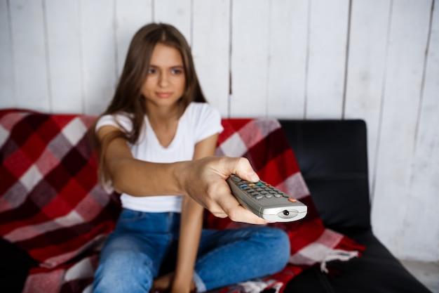 Mulher bonita assistindo tv, sorrindo, sentado no sofá em casa.