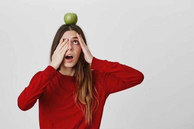 Mulher bonita assustada e nervosa, verificando a maçã na cabeça, boca aberta e ofegante