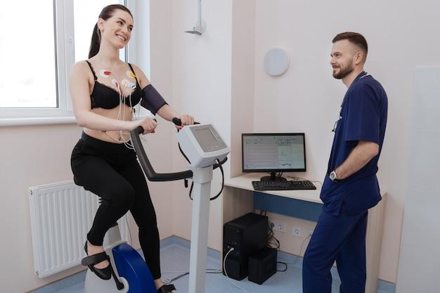 Mulher bonita, ativa e animada realizando alguns exercícios cardiovasculares enquanto o médico examina seus resultados e tira conclusões